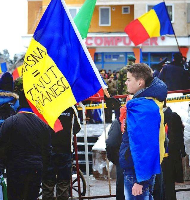 1 decembrie 2014, Sfântu Gheorghe. Cosmin flutură drapelul României de Ziua Națională în piața centrală (FOTO: facebook.com)